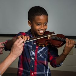 Image of Academy of Strings music lessons instructor assisting student playing violin