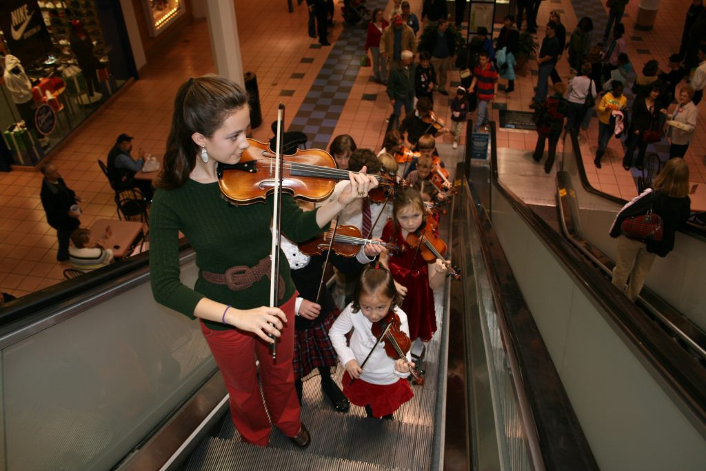 Image of young Academy of Strings students performing violin in the mall for Christmas