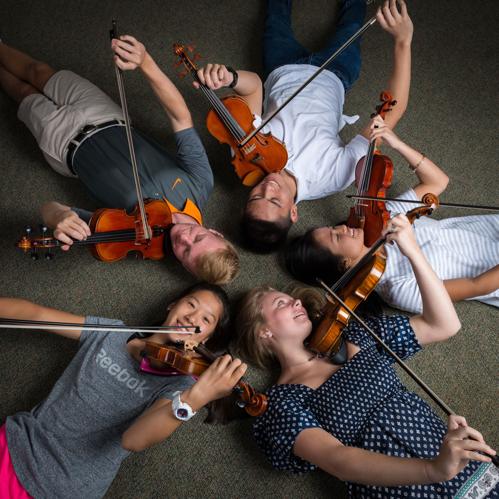 Image of Academy of Strings students playing violin in a music lesson