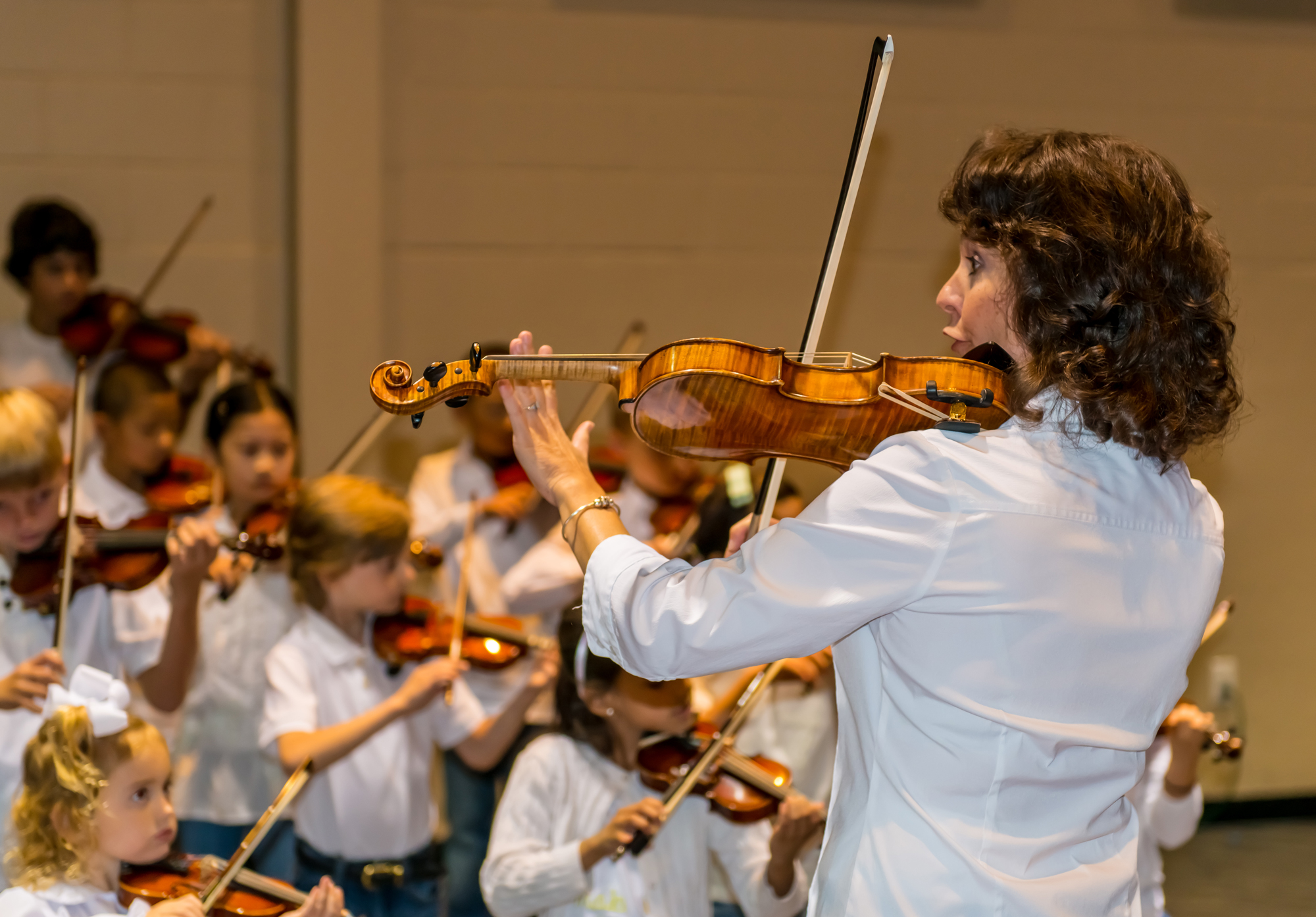Image of Academy of Strings instructor teaching students to play the violin using the Suzuki Method